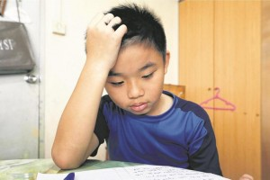 Tay Danzel, 10 trying to concentrate on his homework. More than a third of lower primary school pupils are not getting enough sleep, but only 8 per cent of parents recognise that their child may have sleep problems. -- ST PHOTO: CHEW SENG KIM